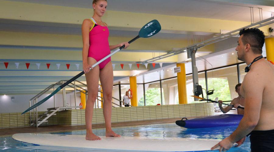 Frau steht auf einem Surfbrett im klinikeigenen Schwimmbad