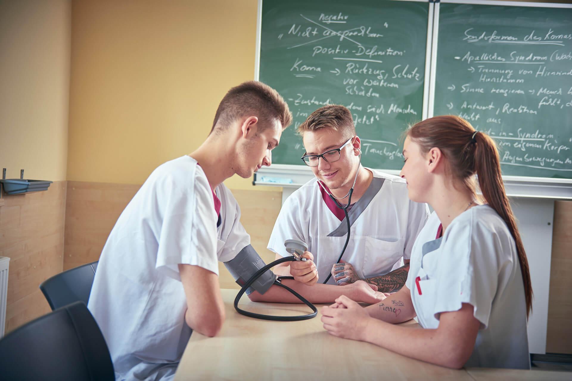 Auszubildene messen sich gegenseitig den Blutdruck